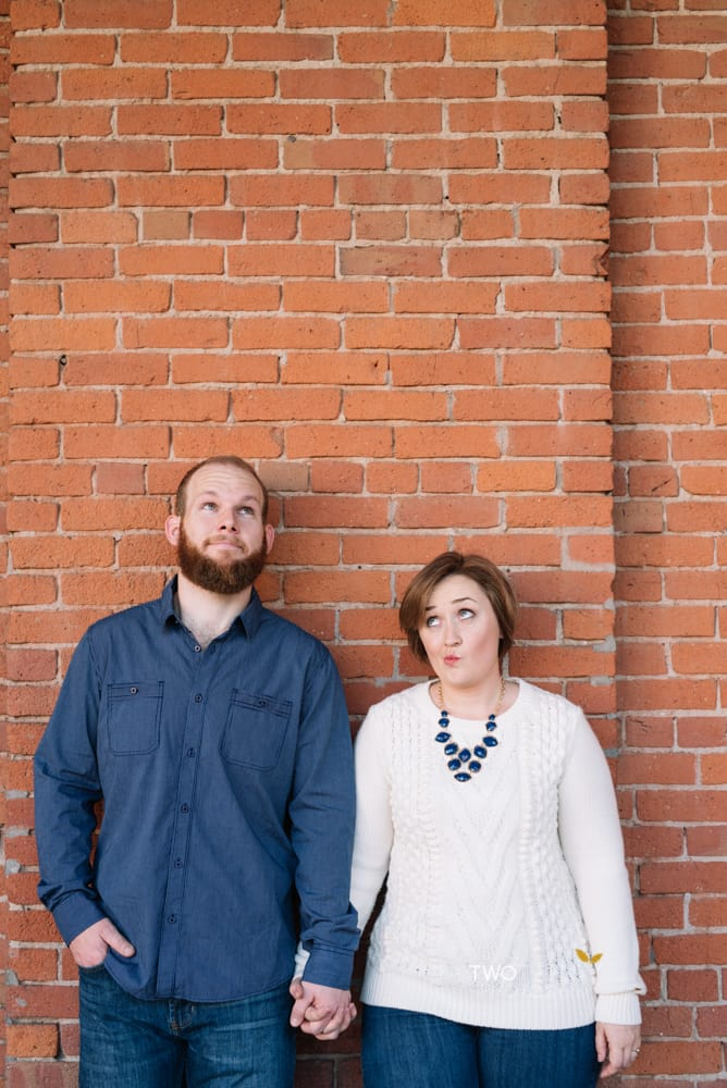 Anniversary portrait photos in old sacramento red brick wall silly faces